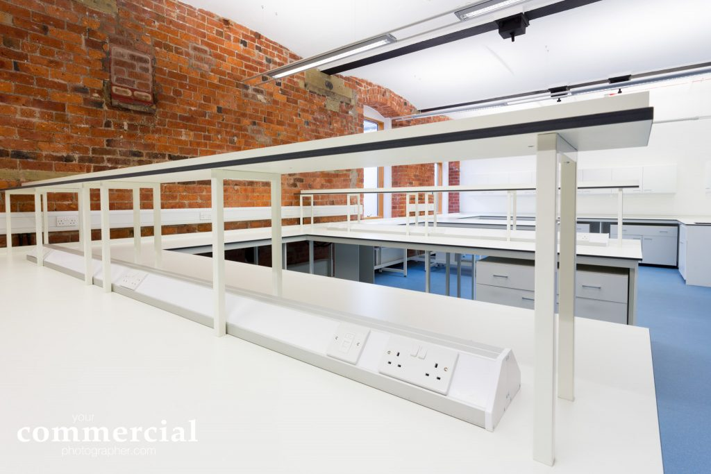 Close up photo showing shelving , power sockets and more workstations behind in a West Yorkshire laboratory.